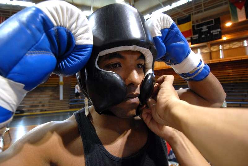 boxeur qui s'equipe avec casque de boxe avant combat